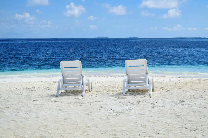 easy chairs on pearly white sands and turquoise waters beyond in maldives