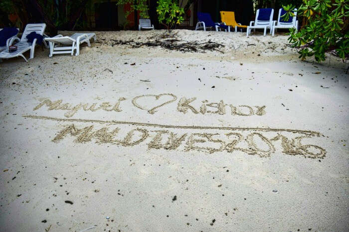kishor & wife writing their names in the white sands of maldives