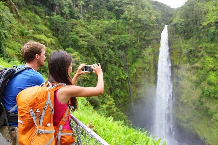 A couple taking pictures of Akaka Falls waterfall on the Big Island on their honeymoon in Hawaii