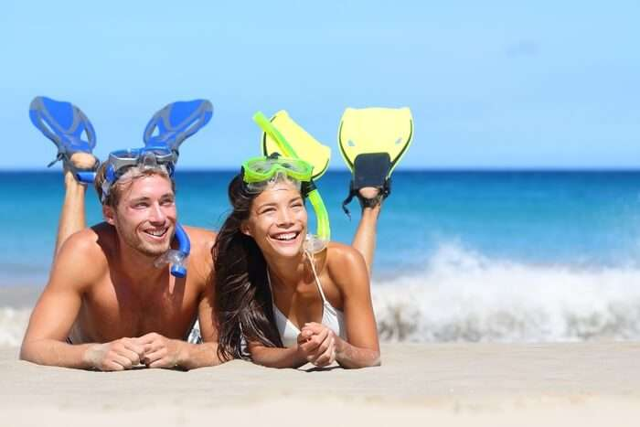 A couple relaxing on a beach after snorkeling in Hawaii