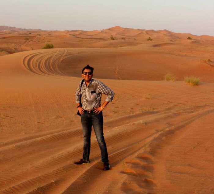 Standing in the vast, golden Arabian desert for our Desert Safari tour