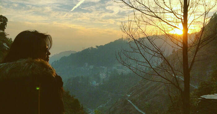 Priyanka standing on a mountain facing sunrise in Mcleodganj