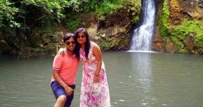 Shashi with his wife standing near a waterfall in Mauritius