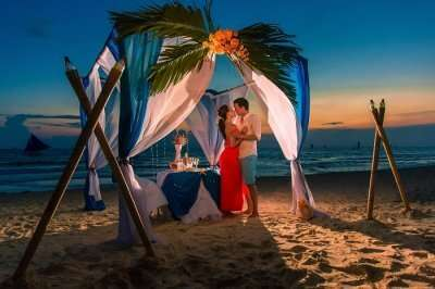 Young beautiful couple have a romantic dinner at sunset on a tropical beach
