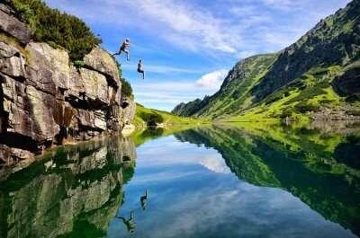 Couple enjoying cliff diving on honeymoon