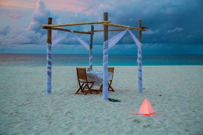 Romantic dinner for two on the beach by the ocean during sunset