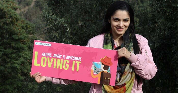 Vandana holding a banner and posing for a photograph during a family trip to Dhanaulti
