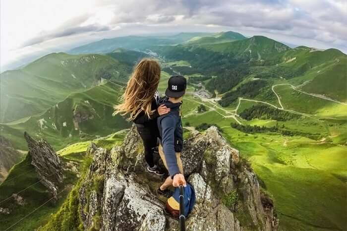 A daring couple on mountain top