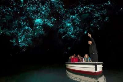 Travelers taking a tour of the Waitomo Glowworm Caves in New Zealand