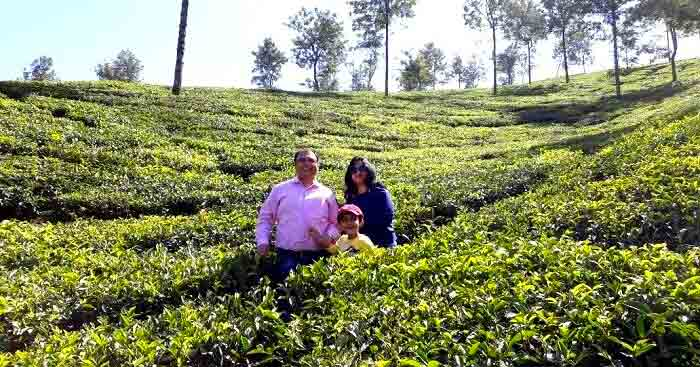 A family standing amidst tea plantation in Kerala