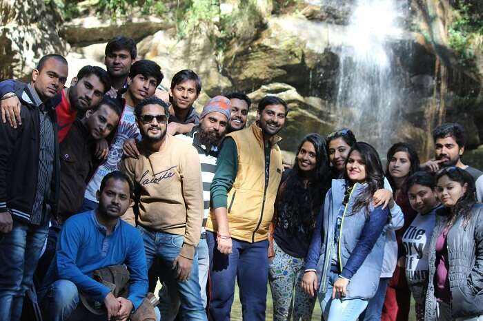 A group of tourists pose in front of a waterfall on their weekend trip to Mukteshwar