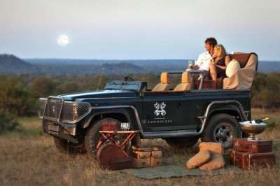 Couple on a gypsy watching sunset during their safari honeymoon in South Africa