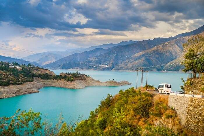 A bus heading to Kanatal with Tehri Dam is the background