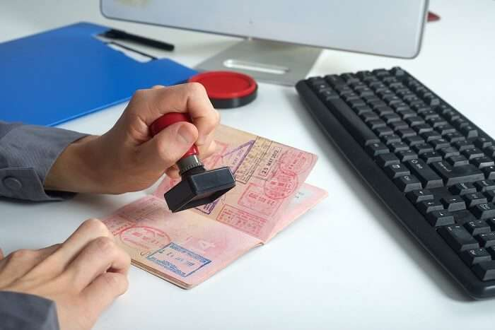 Immigration officer stamping the VISA-on-arrival on the passport