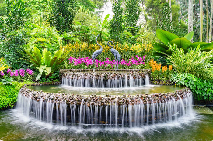 a fountain with pink flowers on the top
