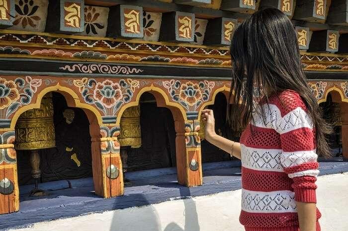 solo female traveler exploring a Buddhist temple in Bhutan