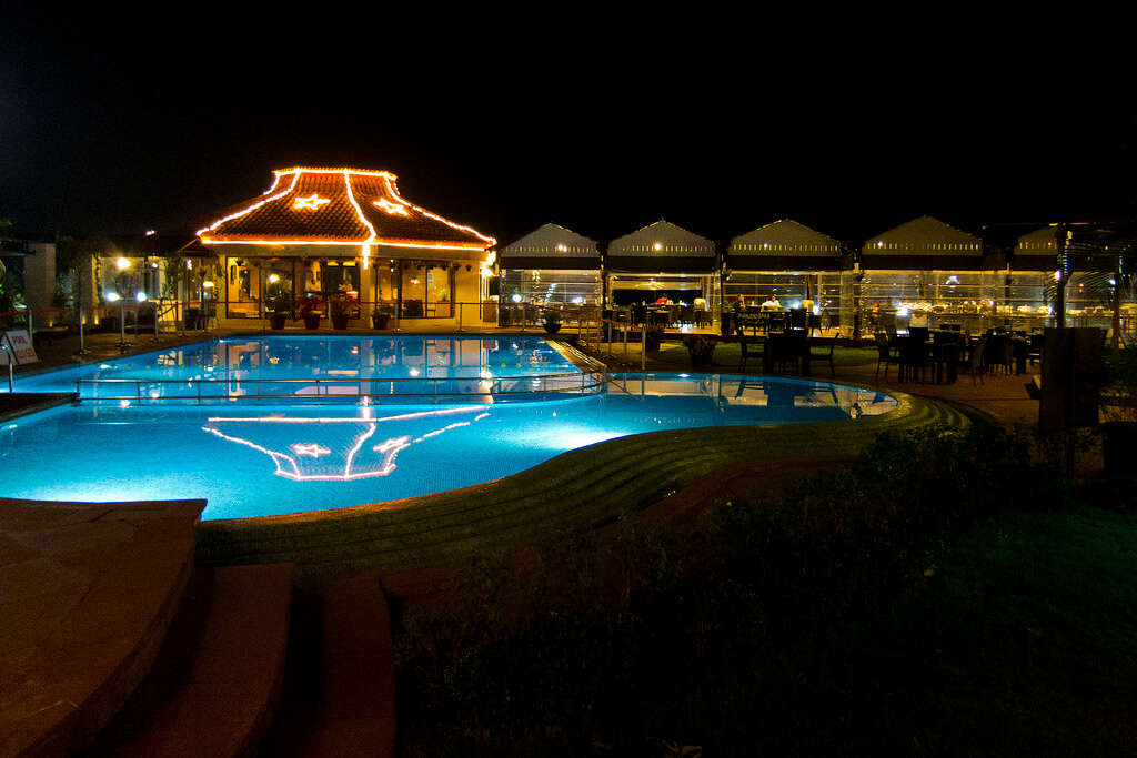 an outdoor poor with a villa resort decorated with lights