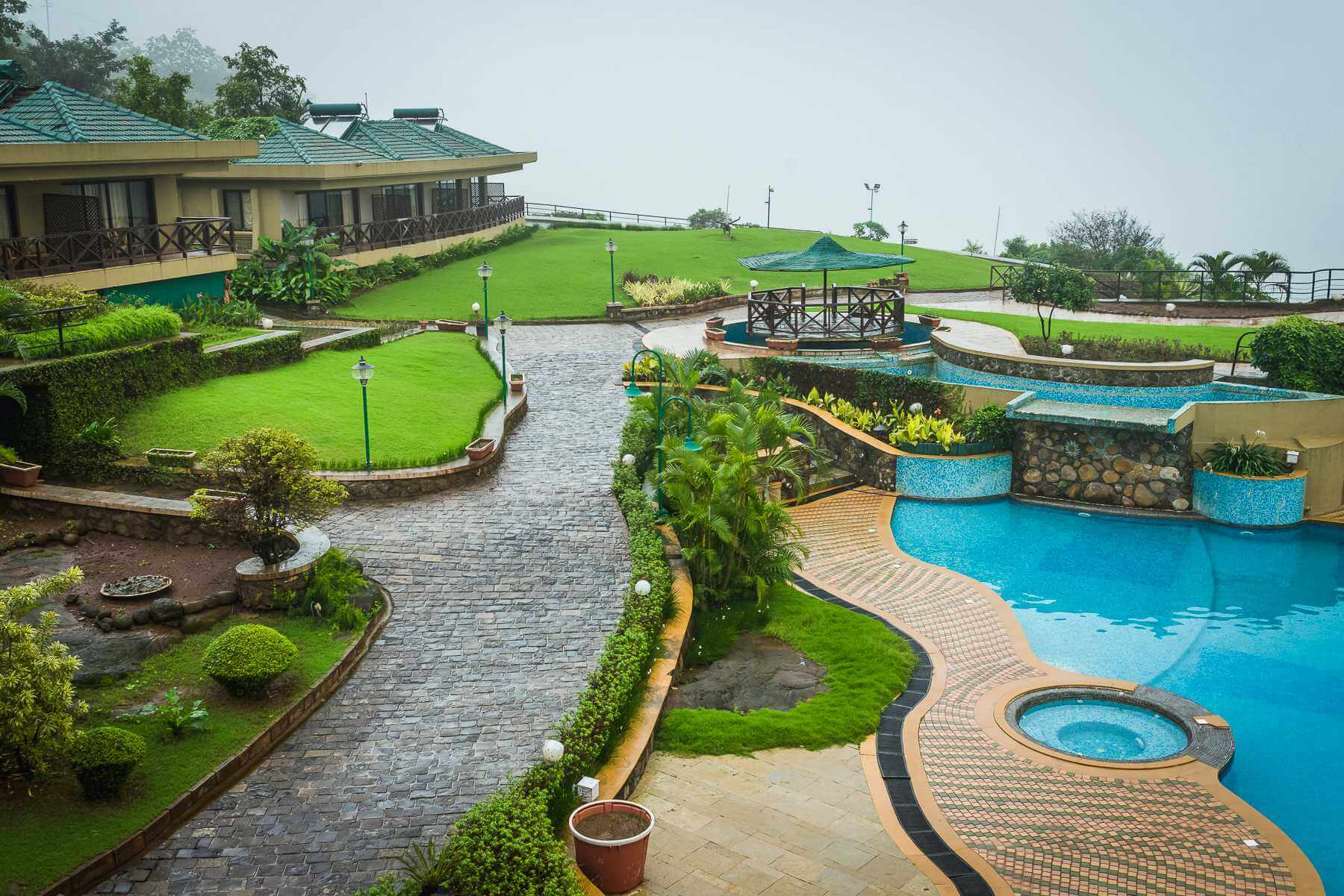 a green premises of a resort in with outdoor pool