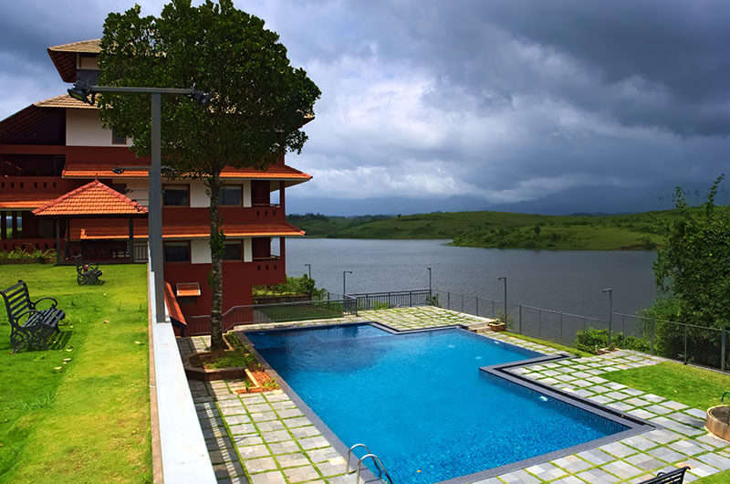 Open air pool area of Vistara Resorts by the lake in Wayanad