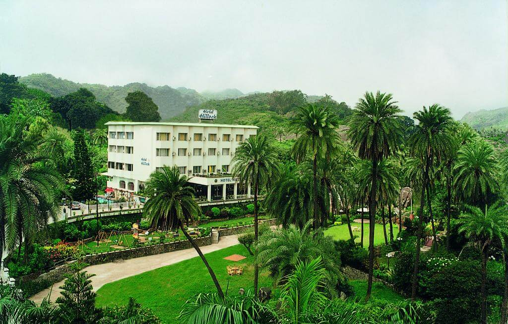 Hotel Hillock white colour building with palm trees in front