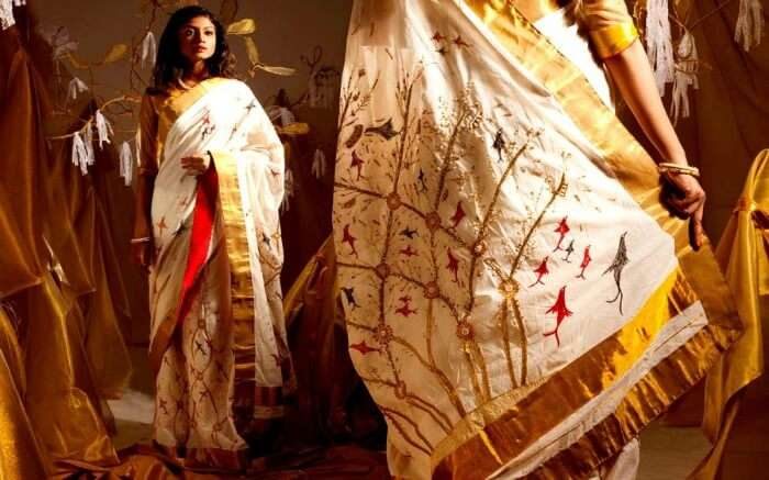 a lady wearing saree looking in mirror