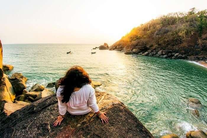 A traveler enjoying a sunset at the Butterfly beach in Goa