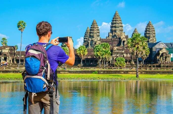 Young man taking a photo of Angkor Wat temple in Cambodia