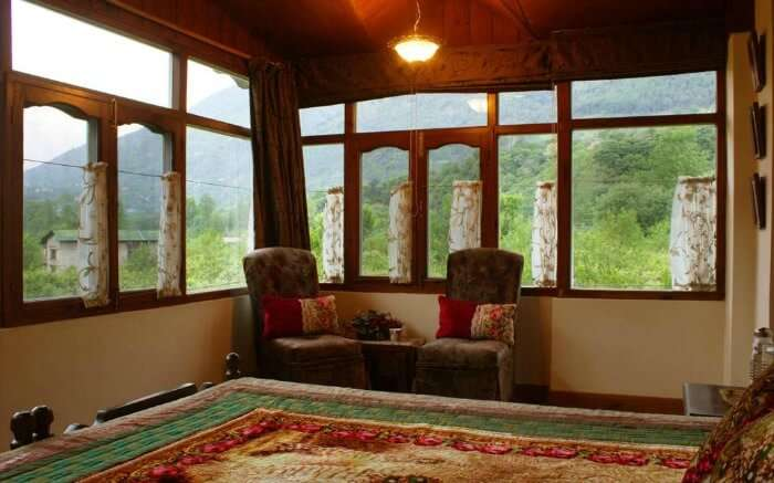 A cozy room with windows in Our Place Himalayas - a popular farmstay in Manali