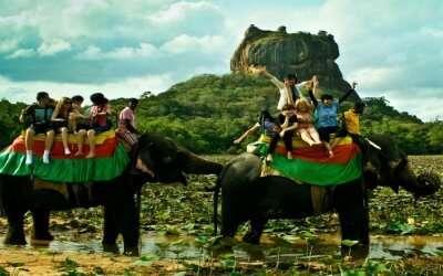 Ecstatic tourists taking joyride on elephants in Kandy