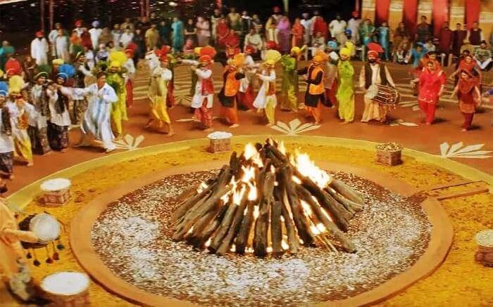 people dancing around Lohri fire