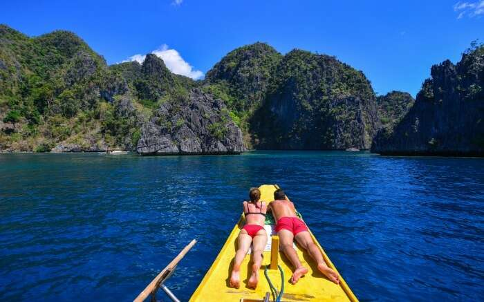 A couple enjoying a boat ride on their Philippines honeymoon