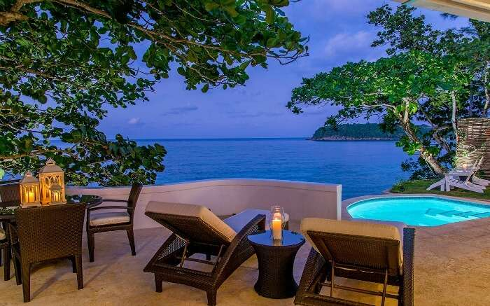 A swimming pool and comfortable sundecks in balcony of a resort in Jamaica