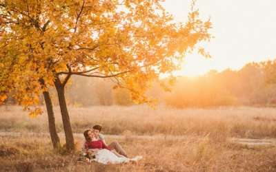 Couple romancing under a maple tree in autumn