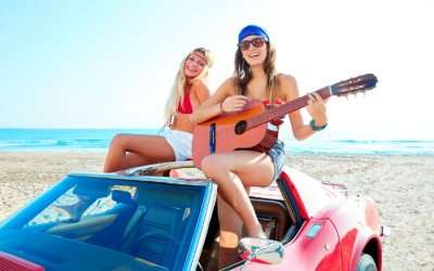Girls on a beach having fun with guitar