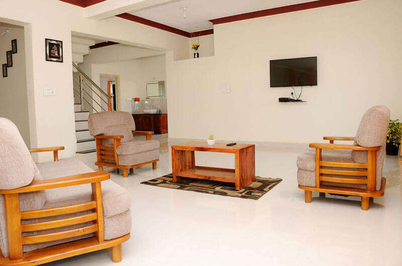 furniture inside a homestay and a tv hung on wall