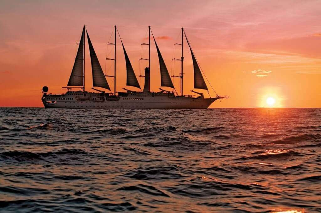 a cruise sailing on water during sunset