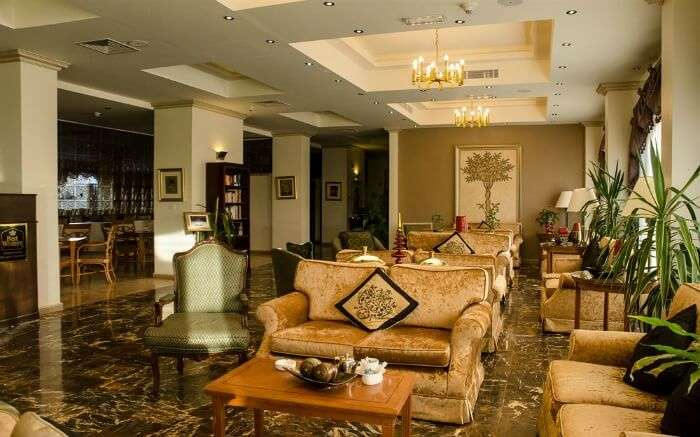 beautiful chandeliers and luxurious couch in a lobby of a hotel