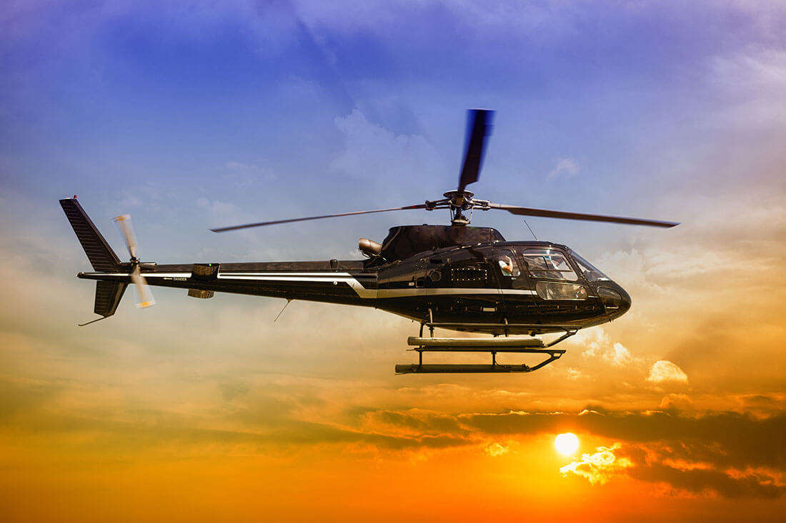 a helicopter flying in a blue and orange sky