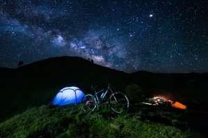 A night shot of a tent set up near Prashar Lake under the starry sky