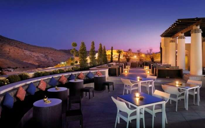 romantic sitting area of terrace overlooking mountains at night