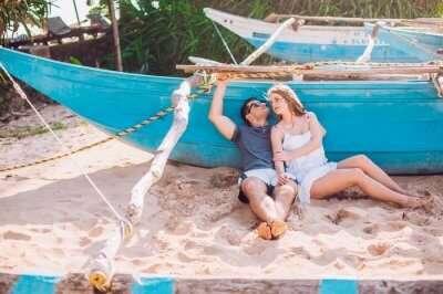 a couple sitting near a blue boat on a beach