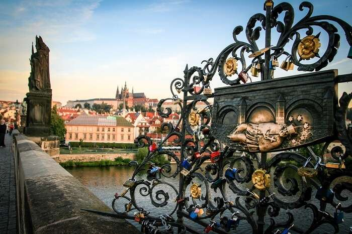 Love locks on the Charles Bridge in Prague at sunrise with Prague Castle in the background