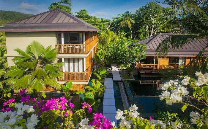 A beautiful hotel surrounded by trees and flower plants
