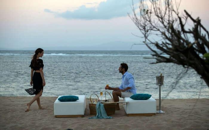 A honeymoon couple enjoying drinks on a beach