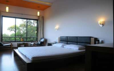 A hotel room with a double bed and a glass window