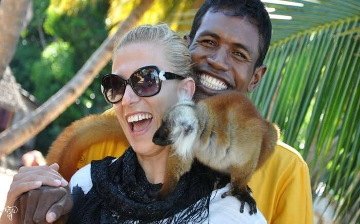 A traveler playing with a lemur in Lokobe Nature Reserve in Madagascar