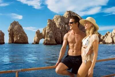 A couple on a honeymoon in Mexico taking a cruise ride near El Arco de Cabo San Lucas at Los Cabos