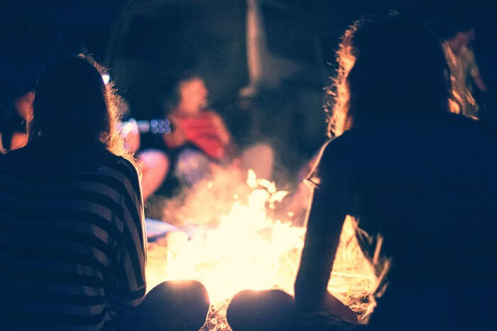 A group of friends enjoying bonfire party on a weekend trip