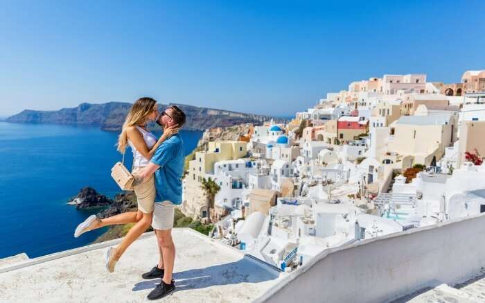 Young couple looks down on the landscape of the island of Santorini ss08082017