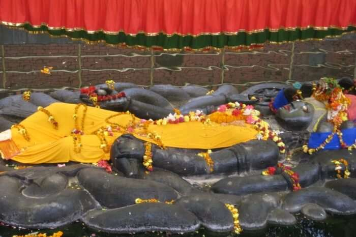 A black stone statue of a god wearing flowers and a yellow sheet